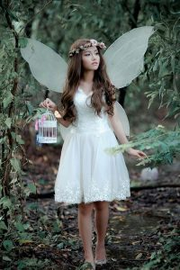 A girl holding white bird cage in a forest