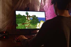 Young man playing Minecraft on his PC