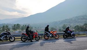 Group of people riding motorcycles in the tropics